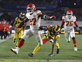 In this Nov. 19, 2018, file photo, Kansas City Chiefs running back Kareem Hunt scores a touchdown ahead of Los Angeles Rams free safety Lamarcus Joyner as Chiefs offensive guard Cameron Erving (75) looks on during the first half of an NFL football game, in Los Angeles.
