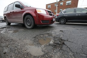 Cars try to dodge a series of potholes along O'Connor Dr. near St. Clair Ave. E. during afternoon rush hour in East York on Wednesday March 13, 2019. (Jack Boland/Toronto Sun/Postmedia Network)