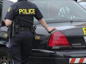 A suspect sits inside an OPP cruiser on May 28, 2014. (Dave Thomas, Toronto Sun)