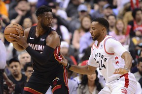 Miami Heat guard Dwyane Wade looks for a pass as Toronto Raptors' Norman Powell defends during Sunday's game. (THE CANADIAN PRESS)
