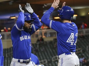 Blue Jays' Teoscar Hernandez, left, celebrates his go-ahead three-run home run off Twins' pitcher Adalberto Mejia with Randal Grichuk in the eighth inning of an MLB game Monday, April 15, 2019, in Minneapolis.
