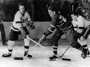 Canadian hockey player Red Kelly (left) of the Detroit Red Wings battles with Paul Masnick of the Montreal Canadiens for an airborne puck while Red Wing Marty Pavelich (right) skates in to join the action during the final game of the Stanley Cup in Detroit, Michigan, April 16, 1954. Detroit went on to win the game and the Cup.