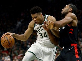 Bucks' Giannis Antetokounmpo (left) dribbles the ball while being guarded by Raptors' Kawhi Leonard in the fourth quarter during Game 2 of the NBA's Eastern Conference Finals at the Fiserv Forum in Milwaukee on Friday, May 17, 2019.
