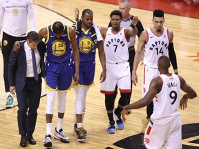 Kyle Lowry #7 of the Toronto Raptors reacts as Kevin Durant #35 of the Golden State Warriors is helped off the court in the first half during Game Five of the 2019 NBA Finals at Scotiabank Arena on June 10, 2019 in Toronto (Photo by Claus Andersen/Getty Images)