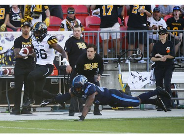 Hamilton Tiger Cats Bralon Addison WR (86) scrampers past a diving Toronto Argonauts Justin Herdman-Reed LB (45) for his third touchdown of the game during the fourth quarter in Toronto, Ont. on Saturday June 22, 2019. Jack Boland/Toronto Sun/Postmedia Network