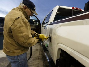 Ron Noble fills up his truck and his auxiliary tank at a Co-op Cardlock station in Lloydminster, Alta., on Dec. 22, 2016.