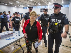 Toronto Sun columnist Sue-Ann Levy is escorted by Toronto Police out of a community meeting at the Birchmount Community Centre in Toronto, Ont. on Wednesday June 12, 2019. The meeting was about the proposed Thunder Woman Healing Lodge & Transitional Housing at 2217 Kingston Rd. in the  Cliffside area of Scarborough.
