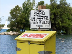 A life preserver box posted with a NO SWIMMING notice on the Detroit River west of the Ambassador Bridge Monday.