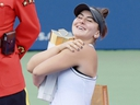 Bianca Andreescu hugs the winner's trophy after Serena Williams withdrew with a back injury during the women's final of the Rogers Cup at Aviva Centre in Toronto on Sunday, Aug. 11, 2019.
