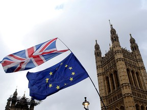 Flags flutter outside the Houses of Parliament, ahead of a Brexit vote, in London March 13, 2019. (REUTERS/Tom Jacobs/File Photo)
