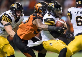 Davon Coleman sacks Tiger-Cats quarterback Jeremiah Masoli during a game last season. The Argonauts have acquired the defensive lineman from the B.C. Lions. (Darryl Dyck/The Canadian Press)