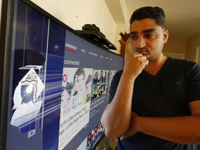 Walli Mohammad looks at a bullet hole in his TV after gunfire erupted at a striple mall at Glencairn and Marlee Aves. sending four people to hospital on Saturday, Aug. 24, 2019. (Jack Boland/Toronto Sun/Postmedia Network)