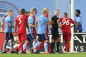 New York City FC and Toronto FC players talk to referee Chris Penso during the second half of Wednesday's game at Yankee Stadium. (USA TODAY SPORTS)