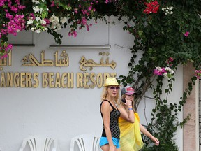 British tourists walk outside the Orange Beach hotel in in Tunisia's coastal town of Hammamet on September 23 2019. - Thomas Cook's 178-year existence was hanging by a thread on Sunday after the iconic British travel firm struggled to find further private investment and is now relying on an unlikely government bailout. Holidaymakers were already reporting problems, with guests at a hotel in Tunisia owed money by Thomas Cook being asked for extra money before being allowed to leave, according to a tourist interviewed by AFP. (ANIS MILI/Getty Images)