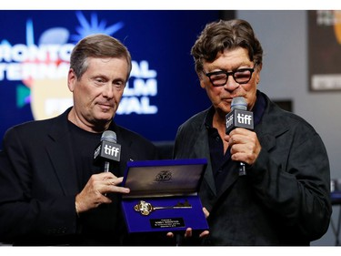 """Musician Robbie Robertson receives the key to the city from Toronto Mayor John Tory during a news conference for the biopic """"Once Were Brothers: Robbie Robertson and The Band"""" at the Toronto International Film Festival (TIFF) in Toronto, Sept. 5, 2019."""