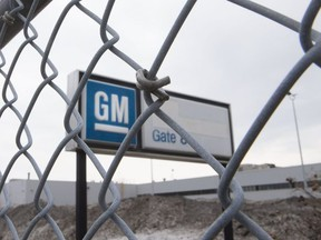 The sign at the GM plant in Oshawa as seen through a fence.