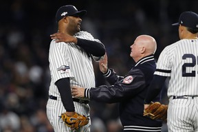 New York Yankees pitcher  CC Sabathia is examined by trainer Steve Donohue after suffering a shoulder injury during Game 4 on Thursday night against Houston. (USA TODAY SPORTS)