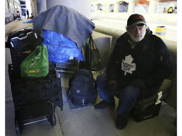 """A homeless man living on Lower Simcoe Street in Toronto on Friday, October 4,  2019. """"Mitch"""" packs up his belongings and waits for city workers to ask him to clear out. He has been evicted seven times, but always returns to the same spot. Veronica Henri/Toronto Sun/Postmedia Network"""