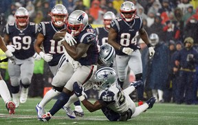New England Patriots running back Sony Michel runs the ball against Dallas Cowboys defensive back Josh Jones and free safety Xavier Woods (25) at Gillette Stadium in Foxboro, Mass., yesterday. The Patriots defeated the Cowboys 13-9. (USA Today)