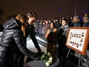 Prime Minister Justin Trudeau and his wife Sophie Gregoire Trudeau lay white roses in front of a photo showing the 14 women who were killed during a vigil on top of Mount Royal marking the thirtieth anniversary of the mass shooting at Ecole Polytechnique, Dec. 6, 2019.  (REUTERS/Christinne Muschi)