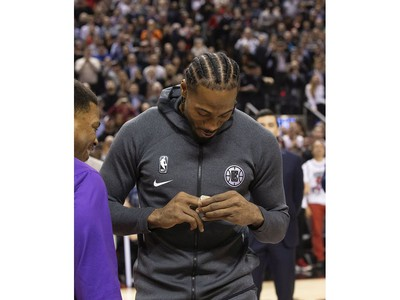 Former Raptors MVP Kawhi Leonard accepts his NBA Championship ring from former team-mate Kyle Lowry before the Raptors / Clippers game in Toronto, Ont. on Wednesday December 11, 2019.