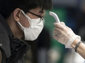 A passenger receives a temperature check before taking a flight bound for Wuhan at Spring Airlines' check-in counter at Haneda airport on January 31, 2020 in Tokyo, Japan.