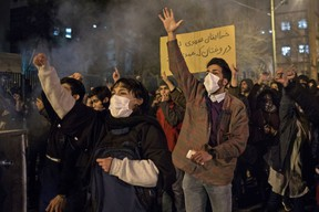 """Iranians chant slogans and hold a placard reading in Farsi """"Your mistake was unintentional, your lie was intentional"""" during a demonstration outside Tehran's Amir Kabir University on January 11, 2020.  (Photo by STR/AFP via Getty Images)"""