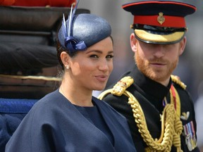 In this file photo taken on June 08, 2019 Britain's Meghan, Duchess of Sussex (L) and Britain's Prince Harry, Duke of Sussex (R) return to Buckingham Palace after the Queen's Birthday Parade, 'Trooping the Colour', in London.