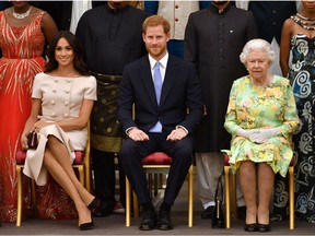 Queen Elizabeth, Prince Harry and Meghan, the Duchess of Sussex, pose for a picture in London, June 26, 2018. *John Stillwell/Pool via Reuters/File Photo)