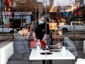 A server attends to customers at a restaurant in the Chinatown district of downtown Toronto, after three patients with novel coronavirus were reported in Canada Jan. 28, 2020.