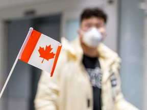 A traveller wears a mask at Pearson airport arrivals, shortly after Toronto Public Health received notification of Canada's first presumptive confirmed case of novel coronavirus, in Toronto, Ontario, Canada January 26, 2020.