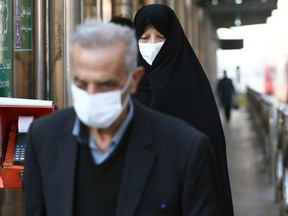 Iranian people wear protective masks to prevent contracting a coronavirus, in Tehran, Iran February 29, 2020.