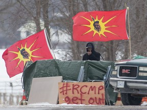 A protester stands between Mohawk Warrior Society flags at a rail blockade on the 10th day of demonstration in Tyendinaga, near Belleville, Ont., Sunday, Feb. 16, 2020.
