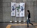 A woman walks past Tokyo 2020 Olympics banners on March 19, 2020 in Tokyo, Japan. As Japanese and IOC officials continued to insist that the Games would go ahead as planned, Japans Deputy Prime Minister said on Wednesday that the Tokyo Olympics are cursed, as speculation grows that the Olympics will have to be postponed due to the ongoing coronavirus (COVID-19) pandemic.