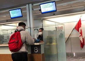 A Canada Border Services Agency (CBSA) officer wears a protective face mask amid coronavirus fears as she checks passports for those arriving at Toronto Pearson International Airport in Toronto, Canada, March 15, 2020.