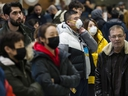 People wear masks as they wait for the arrivals at the International terminal at Toronto Pearson International Airport in Toronto on Saturday, January 25, 2020.