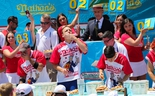Joey Chestnut (C) eats during the men's hot dog eating contest on July 4, 2019 in New York City.