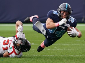 Toronto Argonauts' A.J. Ouellette (34) is tackled by Ottawa Redblacks' Kevin Brown II (31) during second quarter in CFL football action in Toronto on Saturday, Oct. 26, 2019. THE CANADIAN PRESS/Hans Deryk