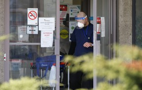 A man exits Eatonville Care Centre on The East Mall in Toronto with a Life Labs specimen bag on Tuesday, April 14, 2020.