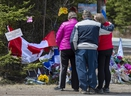 A family pays their respects to victims of the mass killing at a checkpoint in Portapique, Nova Scotia on Friday, April 24, 2020.