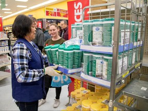 People wait as an employee restocks a shelf with disinfectant wipes at a Walmart Supercentre amid coronavirus fears spreading in Toronto March 13, 2020. (REUTERS/Carlos Osorio)