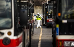 TTC workers wear protective suits inside a bus at the Toronto Transit Commission's Queensway Garage on Evans Ave. near Kipling Ave. in Toronto, Ont. on Thursday, April 16, 2020.