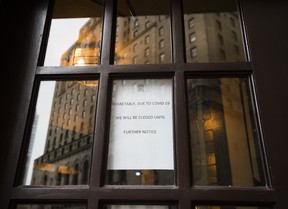 A closed sign is posted at a downtown restaurant due to the coronavirus as the reflection of the Royal York Hotel is shown in the background on Monday, March 23, 2020.