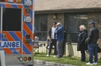 An ambulance drives by as family members look on at Pickering's Orchard Villa long-term care home on Wednesday, May 6, 2020.