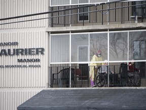 A health care worker wearing personal protective equipment (PPE) works with a resident on a balcony at the Laurier Manor in Ottawa, a long term care facility experiencing an outbreak of COVID-19, on Sunday, April 26, 2020.
