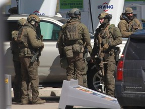 Members of the Royal Canadian Mounted Police tactical unit confer after the suspect in a deadly shooting rampage was neutralized at the Big Stop near Elmsdale, Nova Scotia on April 19, 2020.