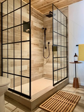 Slick tile, a 'window pane' style shower screen and warm, woodsy accents freshen a formerly lack lustre bathroom. SUPPLIED
