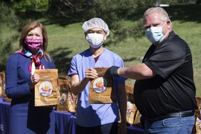 Ontario Premier Doug Ford, right, and Health Minister Christine Elliott pose for a photo with a health-care worker while handing out bagged gifts from Prince Edward Island at Birchmount Hospital, in Scarborough, Ont. on Monday, June 8, 2020.  THE CANADIAN PRESS/Chris Young