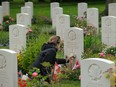 """Lise Belanger, 18, cleans the gravestone of her great-uncle, Roger """"Sonny"""" Firman, at the Commonwealth War Graves Commissions Beny-sur-Mer Canadian War Cemetery in Normandy on June 5, 2019 near Reviers, France."""