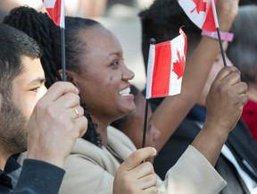 Amarech Yemane Habtemariam (centre) waves her flag as the Institute for Canadian Citizenship, together with Immigration, Refugees and Citizenship Canada, and the National Gallery of Canada, held a special community citizenship ceremony in the Great Hall at the National Gallery of Canada. Photo by Wayne Cuddington/ Postmedia